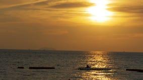 Puesta del sol sobre el mar y la silueta de una pesca del hombre en el displacer Pattaya, Tailandia metrajes