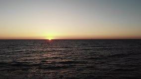Puesta del sol sobre el océano con las ondas que golpean la playa y el pequeño yate en horizonte Puesta del sol con el camino del almacen de metraje de vídeo