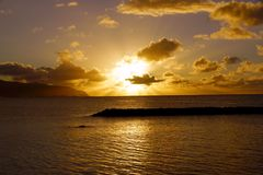 Puesta del sol sobre el océano con las ondas que se mueven a la orilla Fotos de archivo libres de regalías