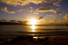Puesta del sol sobre el océano con las ondas que se mueven a la orilla Imágenes de archivo libres de regalías