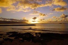 Puesta del sol sobre el océano con las ondas que se mueven a la orilla Fotos de archivo