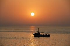 Puesta del sol sobre el océano con un barco Fotos de archivo libres de regalías