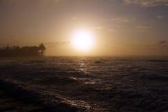 Puesta del sol sobre el océano con las ondas que se mueven a la orilla Fotografía de archivo
