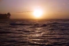 Puesta del sol sobre el océano con las ondas que se mueven a la orilla Imagen de archivo libre de regalías
