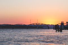 Puesta del sol sobre el puente en una bahía Imagen de archivo