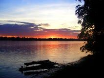Puesta del sol sobre el río Amazonas con un barco de madera Foto de archivo libre de regalías