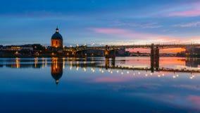 Puesta del sol sobre el río de Garona, con reflexiones del puente del Saint Pierre y de la capilla de San José hÃ'pital de la Gra imagenes de archivo