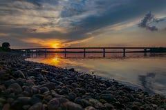 Puesta del sol sobre el río que pasa por alto el puente fotografía de archivo libre de regalías