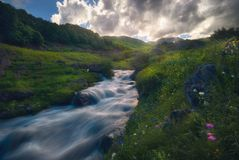 Puesta del sol sobre el río rápido de la montaña Foto de archivo