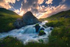 Puesta del sol sobre el río rápido de la montaña imagen de archivo libre de regalías