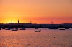 Puesta del sol sobre el río Tejo, 25to de April Bridge y estatua de Fotos de archivo