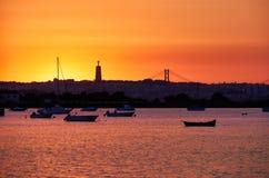 Puesta del sol sobre el río Tejo, 25to de April Bridge y estatua de Imagen de archivo libre de regalías