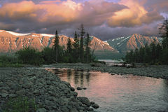 Puesta del sol sobre el río y las montañas Fotos de archivo