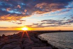 Puesta del sol sobre el rompeolas Fotografía de archivo libre de regalías