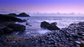 Puesta del sol sobre el terraplén gigante del ` s de la formación de rocas, condado Antrim, Irlanda del Norte