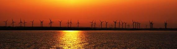 Puesta del sol sobre granja de viento costera imagen de archivo