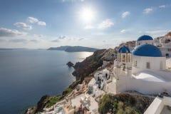 Puesta del sol sobre iglesias abovedadas azules en la caldera en Oia en la isla griega de Santorini imagen de archivo