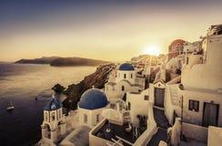 Puesta del sol sobre iglesias azules de la bóveda de Santorini imagen de archivo