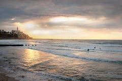 Puesta del sol sobre Jaffa viejo y mediterráneo - personas que practica surf Foto de archivo