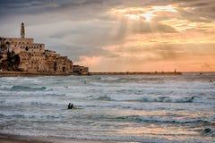 Puesta del sol sobre Jaffa viejo y mediterráneo - personas que practica surf Imagen de archivo