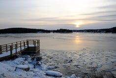 Puesta del sol sobre la bahía del invierno imagenes de archivo
