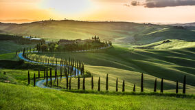 Puesta del sol sobre la carretera con curvas con los cipreses en Toscana fotografía de archivo libre de regalías