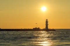 Puesta del sol sobre la entrada de puerto en nde del ¼ de Warnemà imagen de archivo