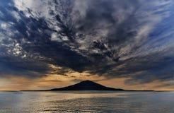 Puesta del sol sobre la isla en el océano azul Fotos de archivo libres de regalías