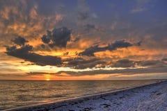 Puesta del sol sobre la playa arenosa Fotos de archivo libres de regalías
