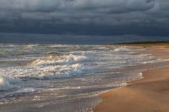 Puesta del sol sobre la playa arenosa y el cielo azul marino antes de la tormenta Imagen de archivo