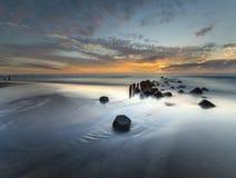 Puesta del sol sobre la playa del mar Imágenes de archivo libres de regalías