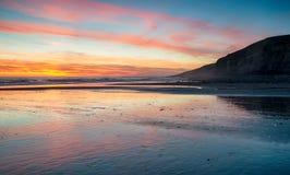 Puesta del sol sobre la playa en la bahía de Dunraven Fotos de archivo libres de regalías