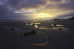 Puesta del sol sobre la playa en la costa oeste de la isla del jersey Fotografía de archivo libre de regalías