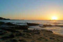 Puesta del sol sobre la playa negra de la roca - Victoria, Australia fotografía de archivo