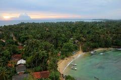 Puesta del sol sobre la playa y la ciudad Fotos de archivo libres de regalías