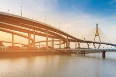 Puesta del sol sobre la suspensión río de la interconexión tendida un puente sobre y de la carretera Foto de archivo libre de regalías