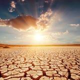 Puesta del sol sobre la tierra agrietada Imagen de archivo libre de regalías