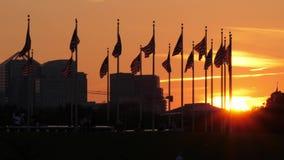 Puesta del sol sobre las banderas americanas en Washington Monument almacen de metraje de vídeo