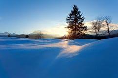Puesta del sol sobre las colinas de la nieve en las montañas Imagenes de archivo