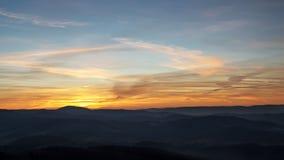 Puesta del sol sobre las colinas en la niebla Imagen de archivo