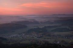 Puesta del sol sobre las colinas en niebla Imagen de archivo