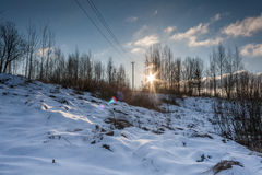 Puesta del sol sobre las colinas nevosas Fotos de archivo libres de regalías