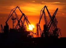 Puesta del sol sobre las grúas del puerto Imágenes de archivo libres de regalías