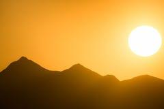 Puesta del sol sobre las montañas debajo del cielo anaranjado Fotos de archivo