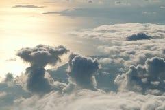 Puesta del sol sobre las nubes de la ventana del aeroplano Foto de archivo