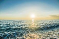 Puesta del sol sobre las ondas del mar Fotos de archivo