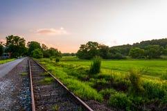 Puesta del sol sobre las pistas de ferrocarril y los campos en el condado de York, PA Foto de archivo libre de regalías