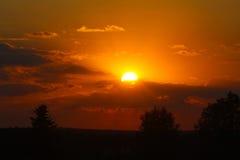 Puesta del sol sobre los árboles Fotos de archivo libres de regalías