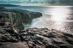 Puesta del sol sobre los acantilados irlandeses Fotos de archivo