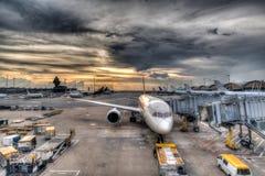 Puesta del sol sobre los aviones comerciales en la pista de despeque del aeropuerto Imagenes de archivo